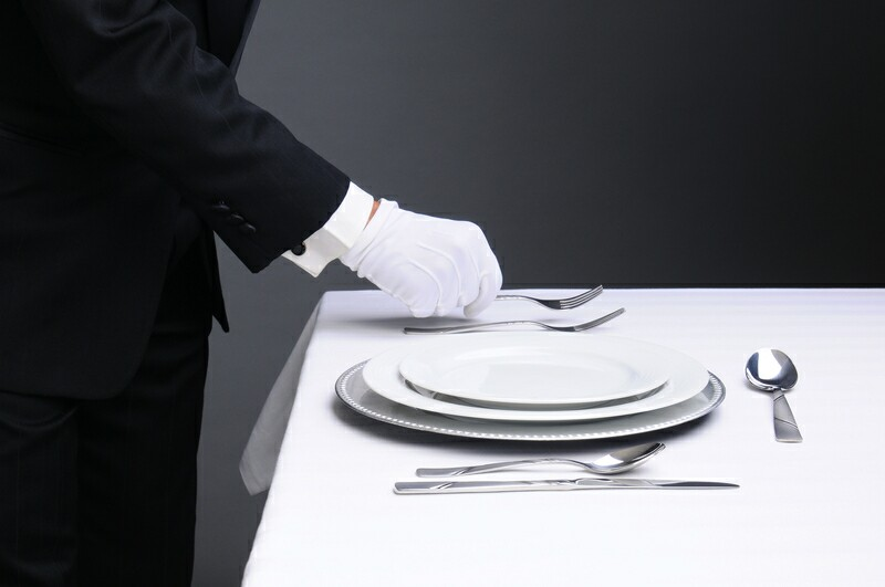 Waiter using white glovess